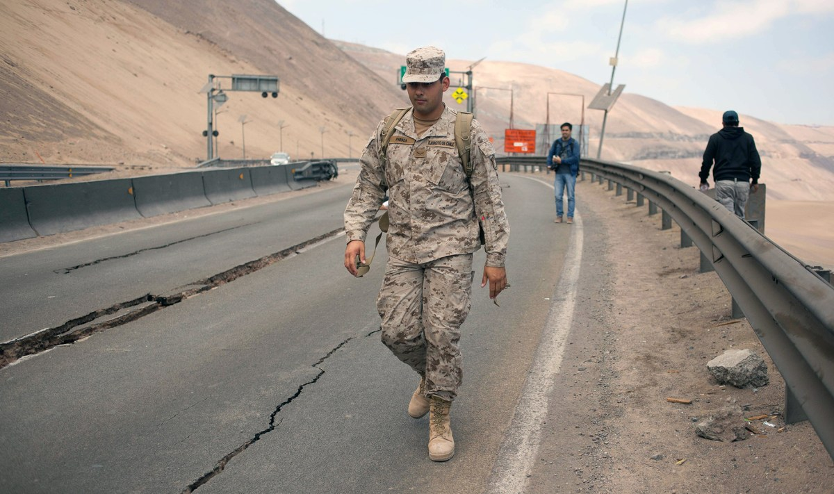 A soldier and other people walk along a road damaged by a powerful 8.2-magnitude earthquake that hit off Chile's Pacific coas