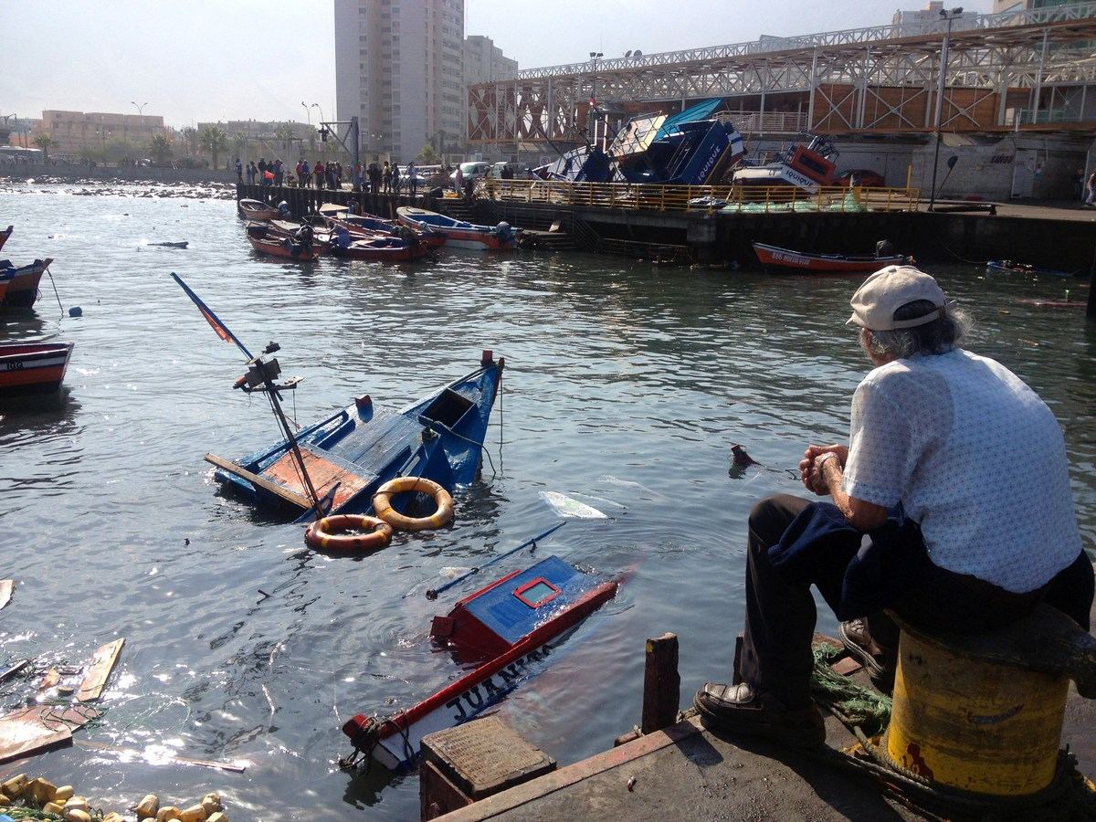 A man looks on April 2, 2014 at fishing boats which sank at the Riquelme Cove, in Iquique, northern Chile, after a powerful 8