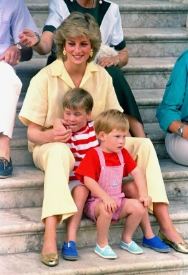 A little younger than the father we now know him to be, Prince William and his brother Prince Harry sit with their mother on