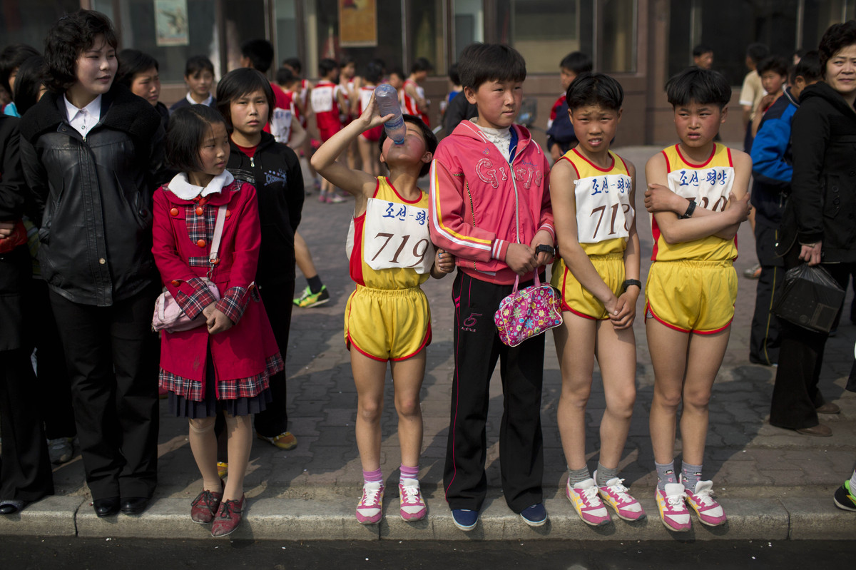 Young North Korean runners rest after finishing their part of the Mangyongdae Prize International Marathon in Pyongyang, Nort