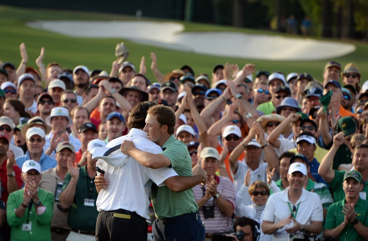 Bubba Watson of the US embraces Jordan Spieth after putting on the 18th green during the 78th Masters Golf Tournament at Augu
