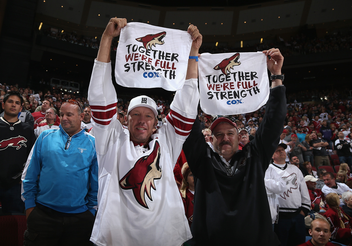 GLENDALE, AZ - APRIL 13:  Fans of the Phoenix Coyotes hold up towels reading 'Together We're Full Strength' during the NHL ga