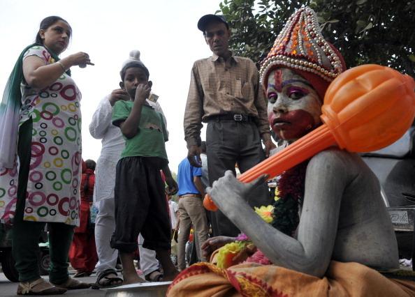 A small boy Rajesh Kumar dressed as a Lord Hanuman sitting near Bangla Sabih Gurudwara on the eve of Hanuman Jayanti on April