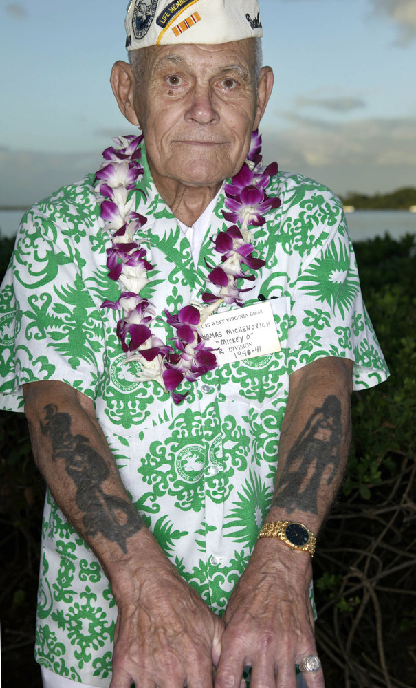 Pearl Harbor survivor Thomas Michenovich shows off his wartime tattoos before the start of a Dec. 7, 2004, ceremony honoring