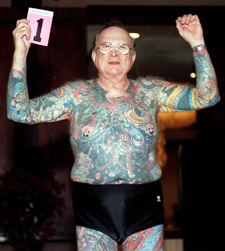 Larry Happ, 68, raises his arms to show his tattoos as he competes in the senior man largest tattoo category at the Los Angel