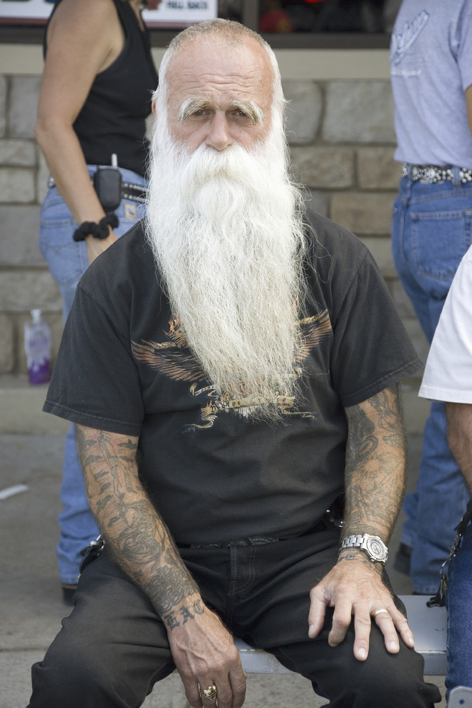 Man with tattoos posing at the Sturgis Motorcycle Rally, Sturgis, South Dakota, in 2007.