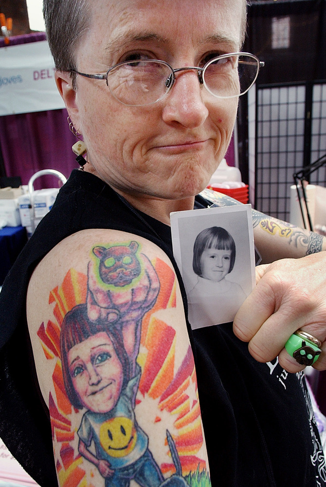Linda May Ellis of Rockland, Mass., poses at a Boston tattoo convention in 2003. Ellis is holding the childhood picture of he