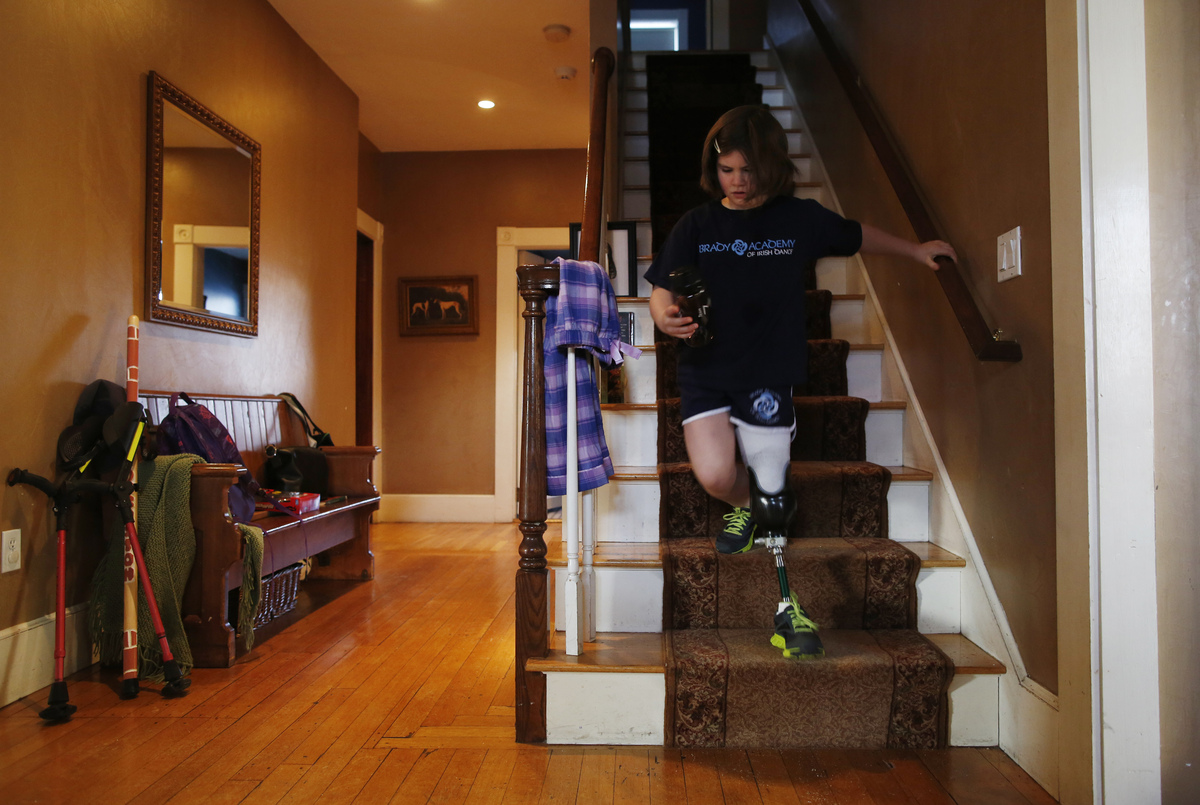Jane Richard runs down the stairs at home as she gets ready to leave for an appointment at Spaulding on February 10, 2014. Ba