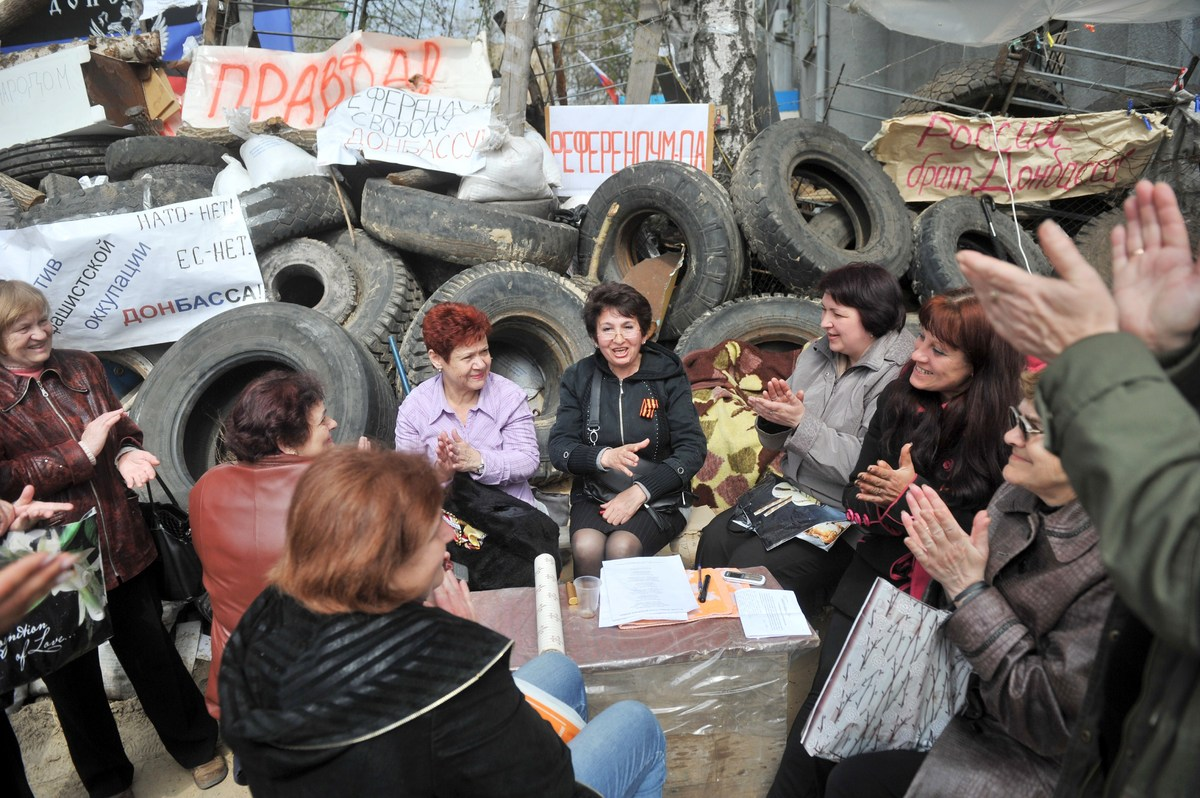Women, pro-Russia supporters applaud as they sit by a barricade outside the police regional building seized by the separatist