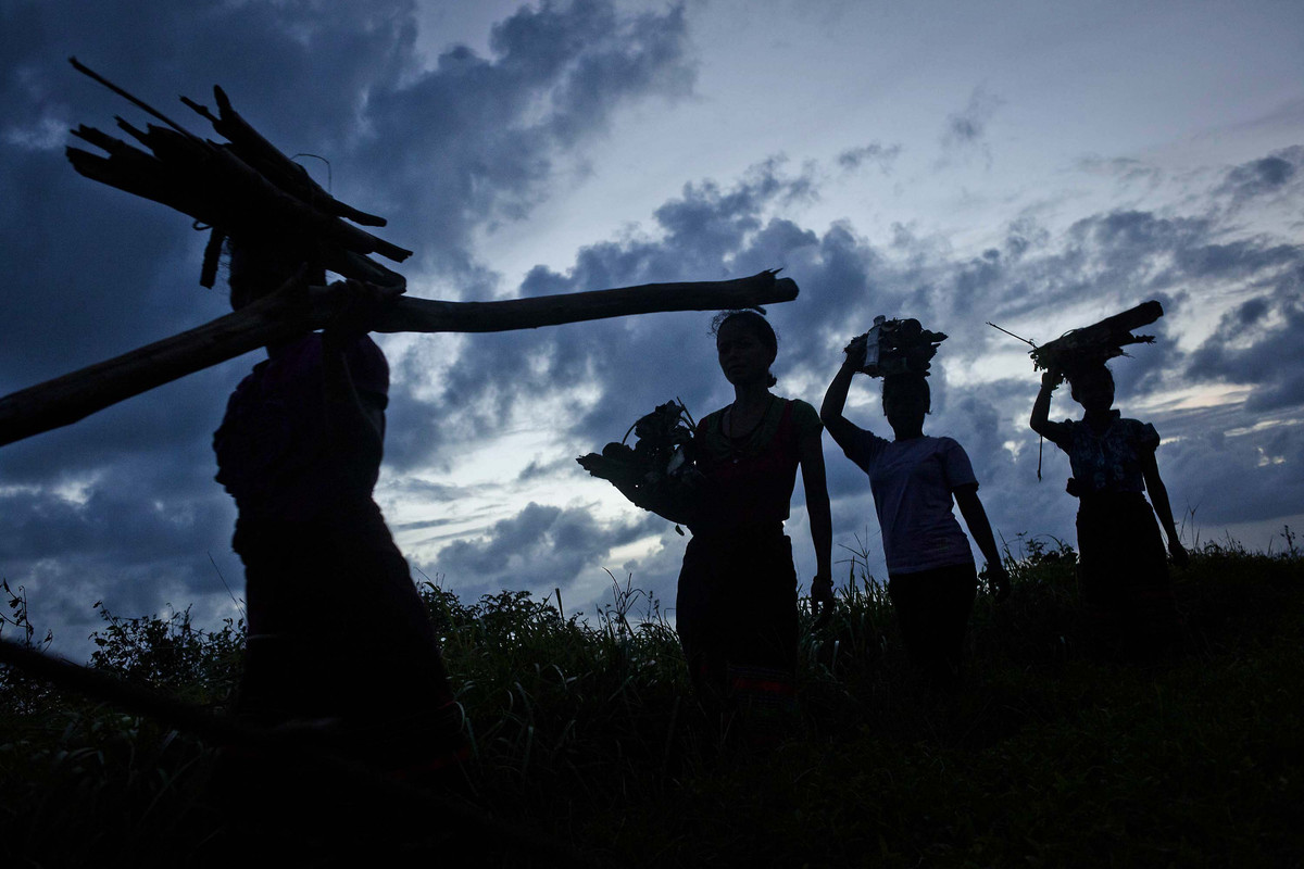Sumbanese women carry wood as prepares for the pasola war festival on the next day at Wainyapu village on March 6, 2013 in Su