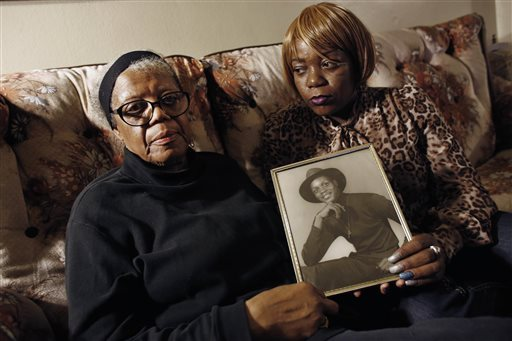 Alma Murdough and her daughter Cheryl Warner hold a photo of Murdough's son, at her home in the Queens borough of New York. J