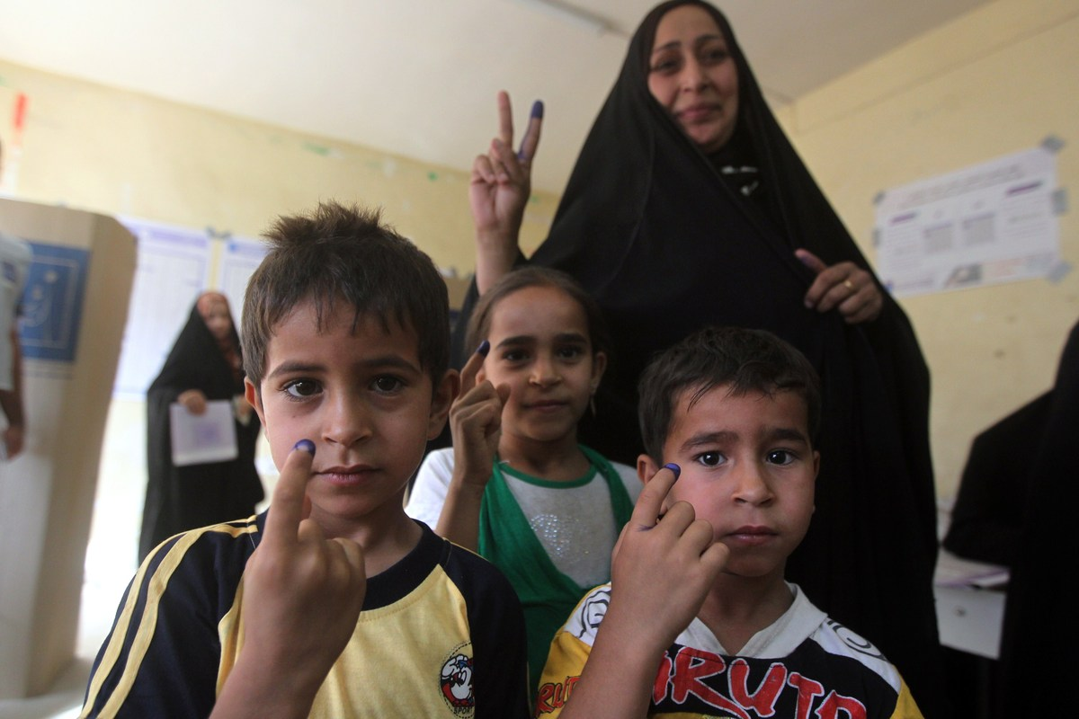An Iraqi woman and her children display ink-stained fingers after she voted in Baghdad's Sadr City district during the countr