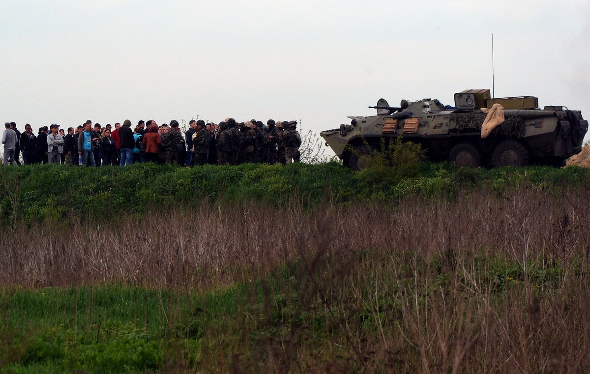 Residents gather to speak to Ukrainian soldiers at a checkpoint which they seized in the early morning in the village of Andr