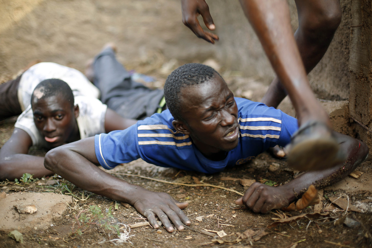 Men duck for cover as heavy gunfire erupts in the Miskin district of Bangui, Central African Republic, Monday, Feb. 3, 2014.