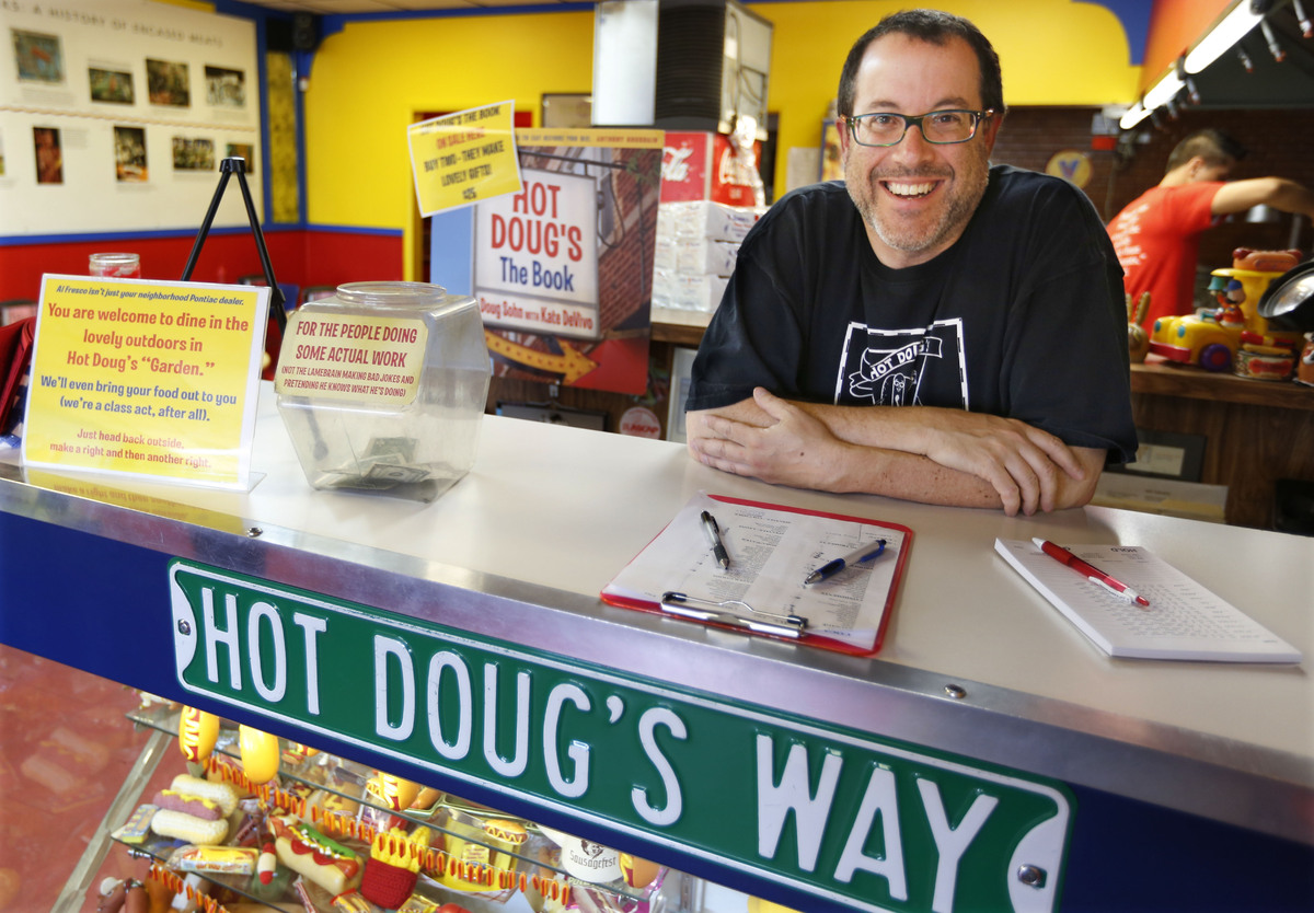 In this Oct. 9, 2013, photo, Doug Sohn, owner of Hot Doug's restaurant on the northwest side of Chicago, poses before busines
