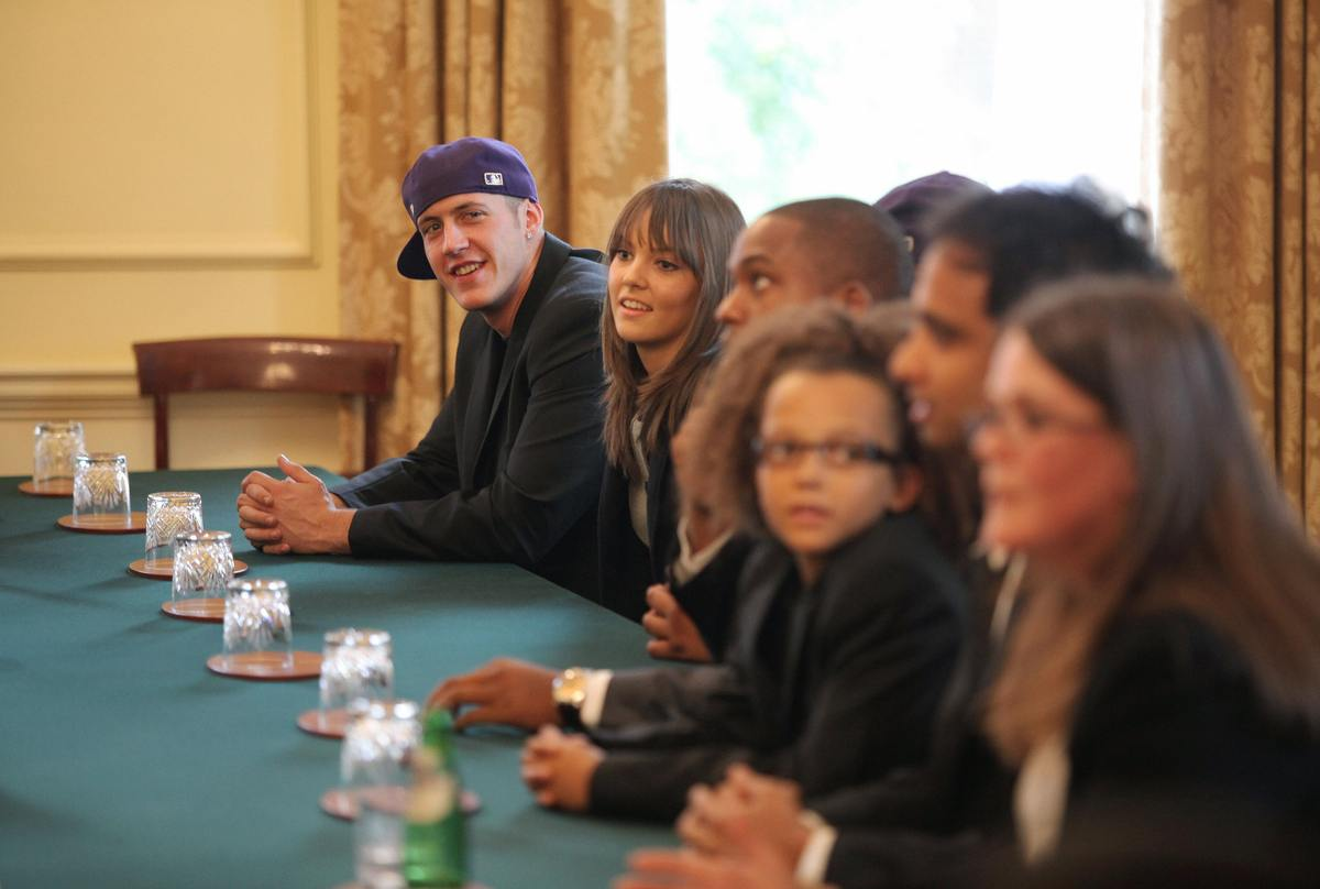 Members of British dance group 'Diversity' take part in a discussion on youth around the Cabinet room table inside 10 Downing