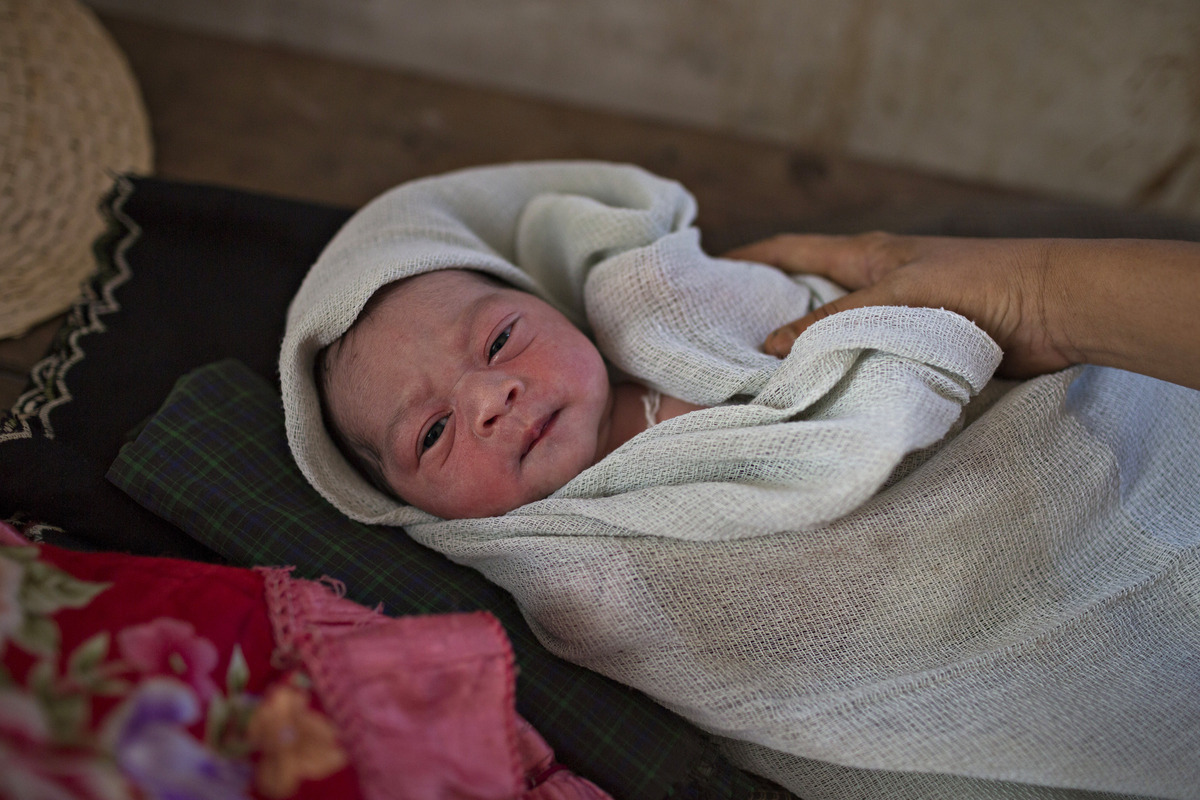 SITTWE, BURMA - MAY 07: A baby, only several hours old, lays on a bed of boards in the Dar Paing Clinic inside the Dar Paing