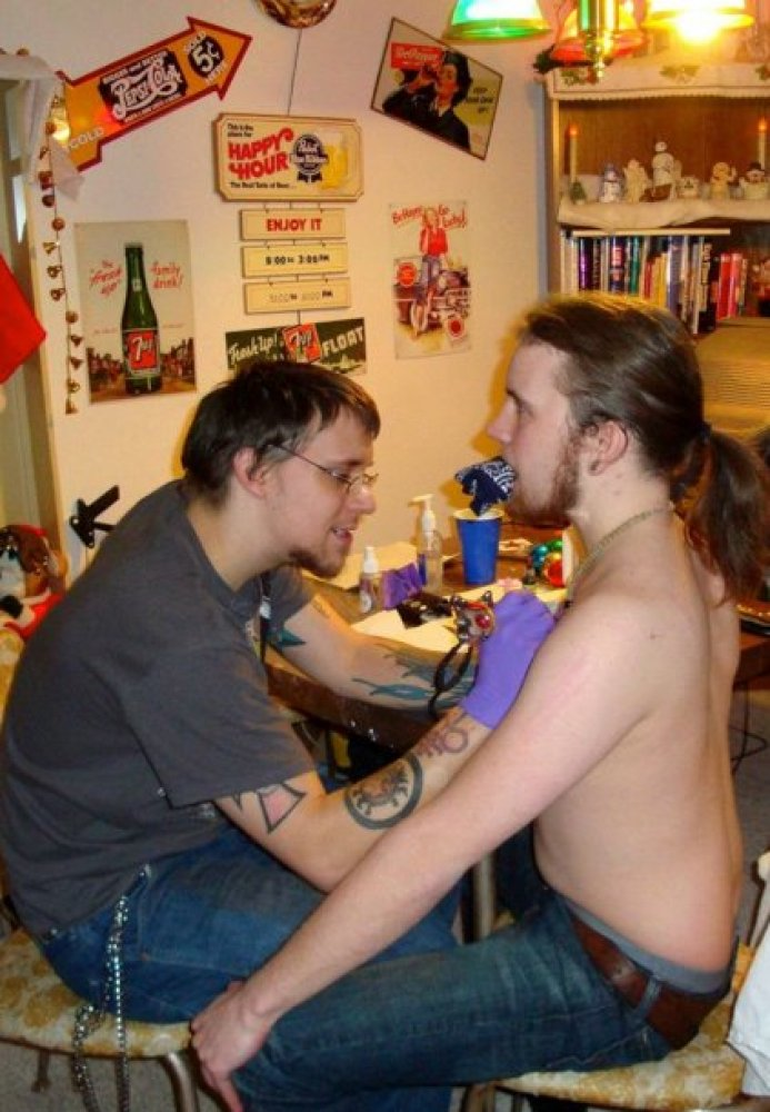 """""""Synyster Ink"""" tattooing a client.  """"How many of your 'clients' commit suicide after you tattooed them?"""""""