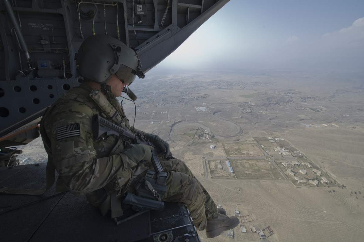 A crew chief assigned to the US Army's 10th Mountain Division rides on the ramp of a CH-47 helicopter. The crew chief perform