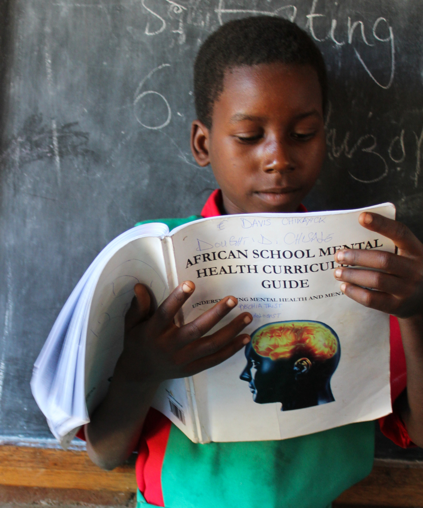 "A boy studies the ""African School Mental Health Curriculum"" made available through a Farm Radio International led program. Th"