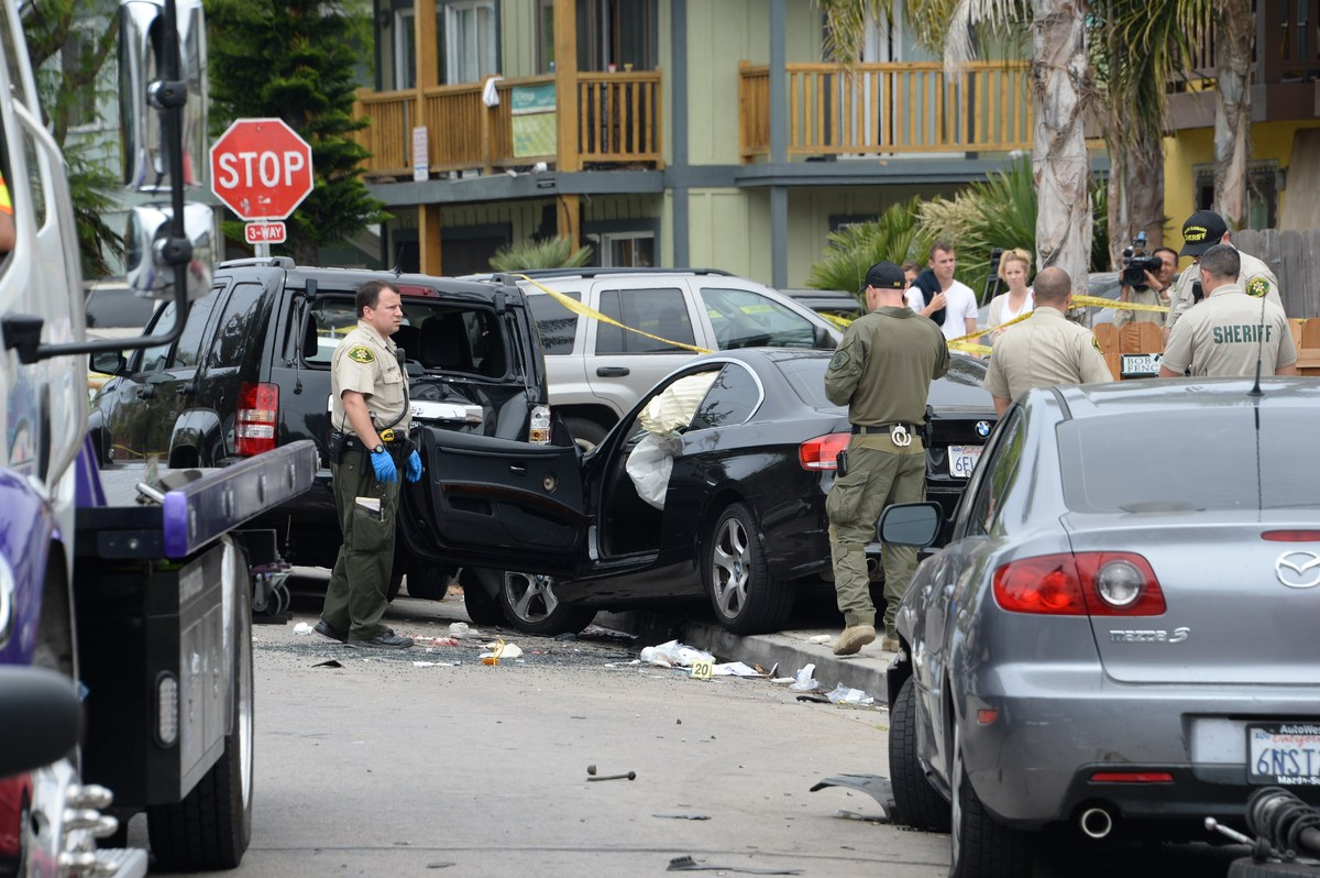 Investigators inspect a suspected gunman's car on May 24, 2014, after a drive-by shooting in Isla Vista, California, a beach