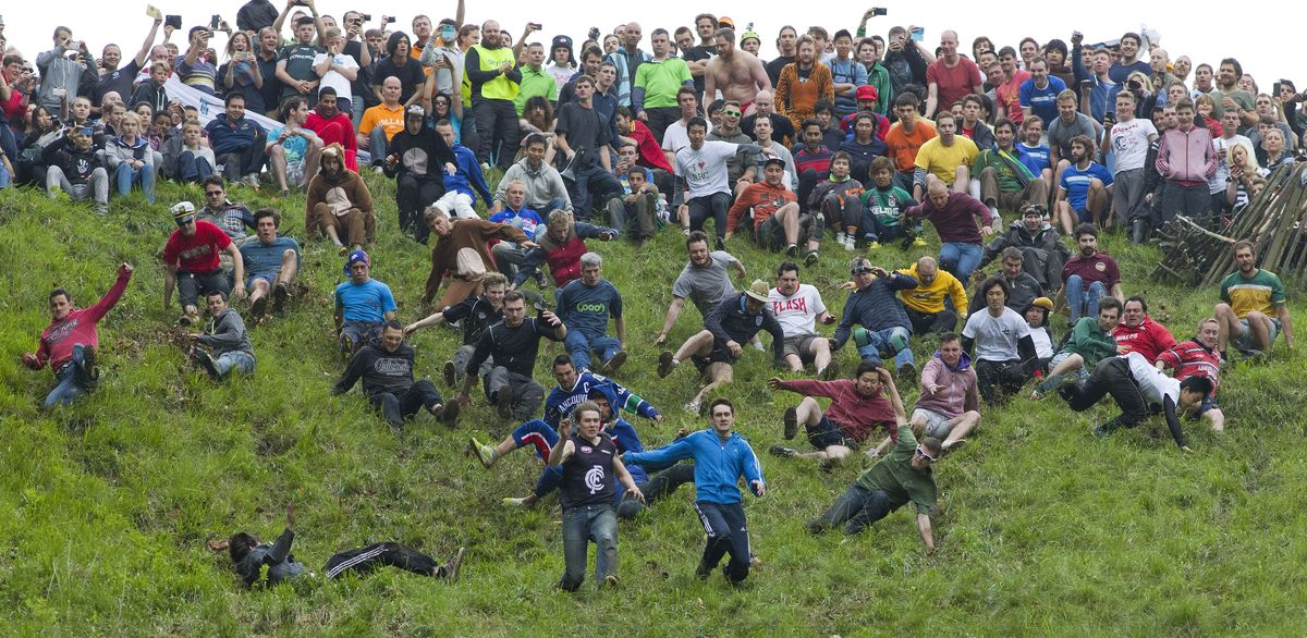Competitors tumble down Coopers Hill in pursuit of a round Double Gloucester cheese during the annual cheese rolling and wake