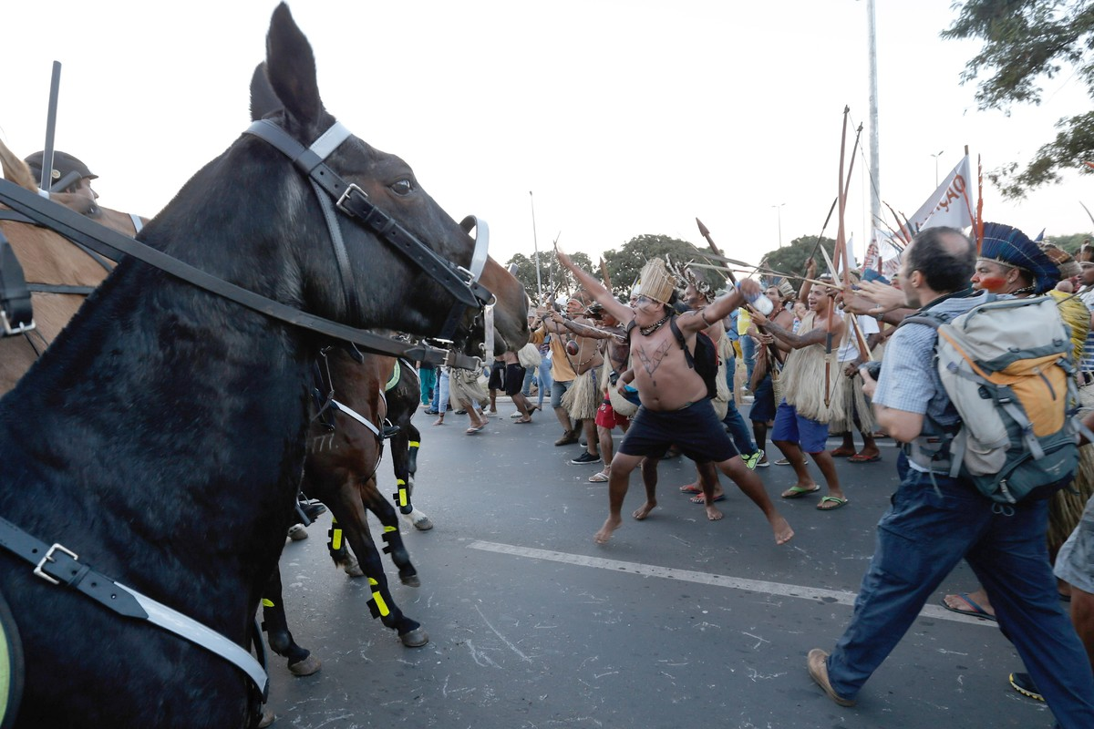 Protesters in traditional headdress squared off against Brazilian police mounted on horses