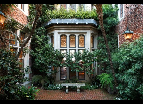 The interior garden courtyard opens through two sets of steel-frame French doors.
