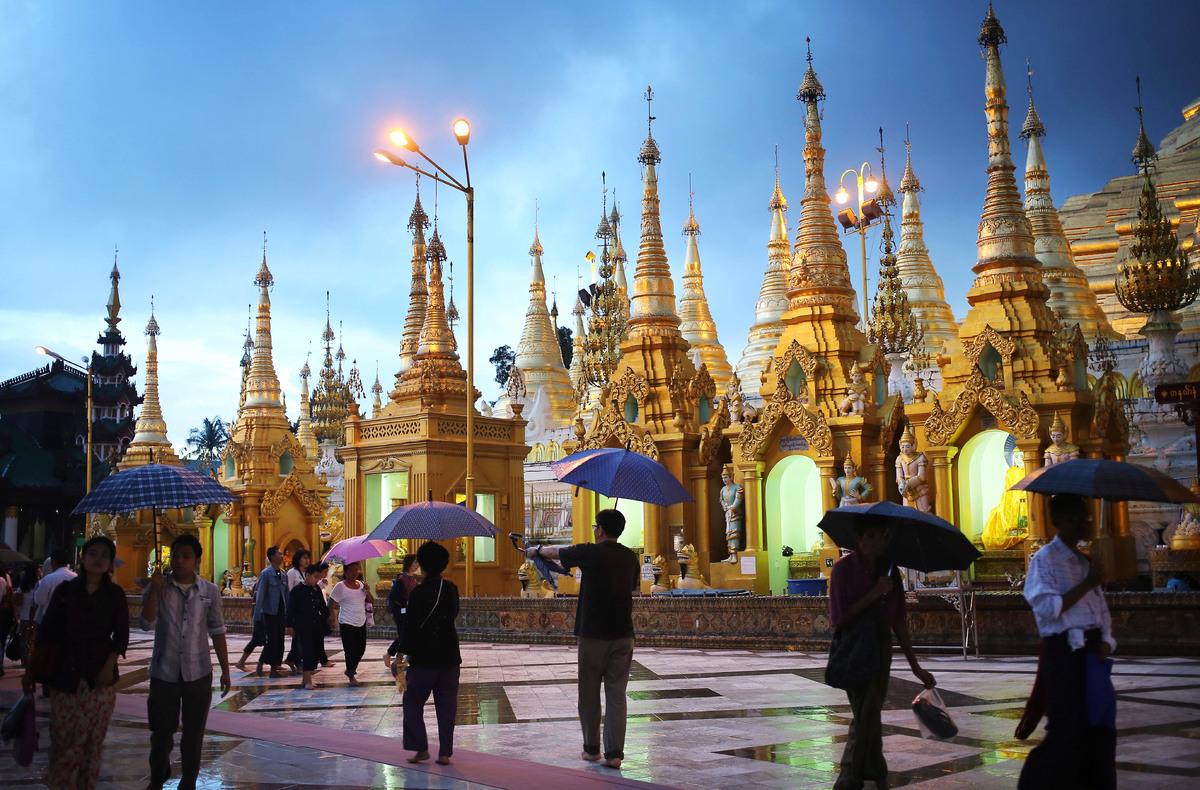 Visitors make their way around the Shwedagon Pagoda despite the rainy weather in Yangon, Myanmar, Sunday, Aug. 11, 2013. (AP
