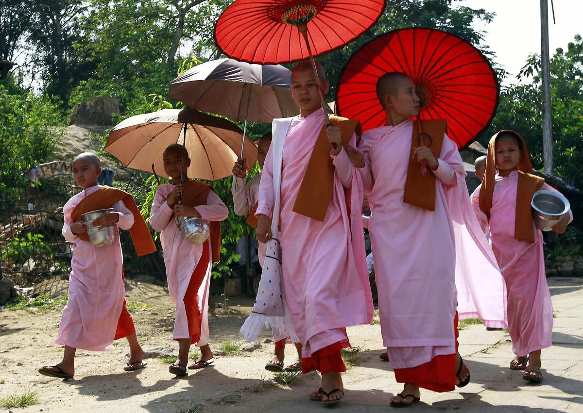 Myanmar's Buddhist nuns walk along a road as they collect alms from devotees Thursday, March 29, 2012, in Yangon, Myanmar.  (