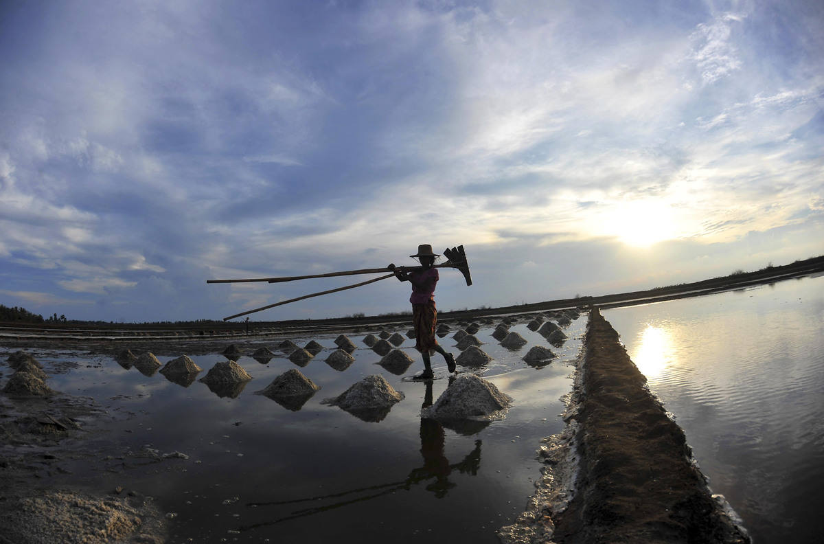 A salt maker walks through a salt field on her way back home in Haigyigyun, Ayeyawady Delta, about 300 kilometers (186 miles)