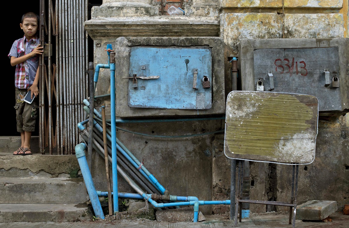 A boy peeks out from an old apartment building, in which water pumps are boxed and padlocked for protection in downtown Yango