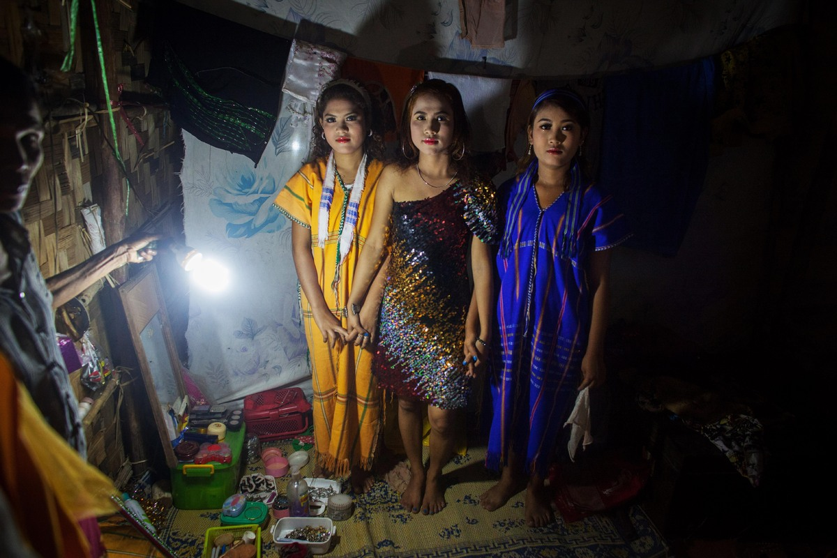 A woman shines a light on three performers posing in traditional dress from the Phoe Chit Naing Orchestra band for a photogra