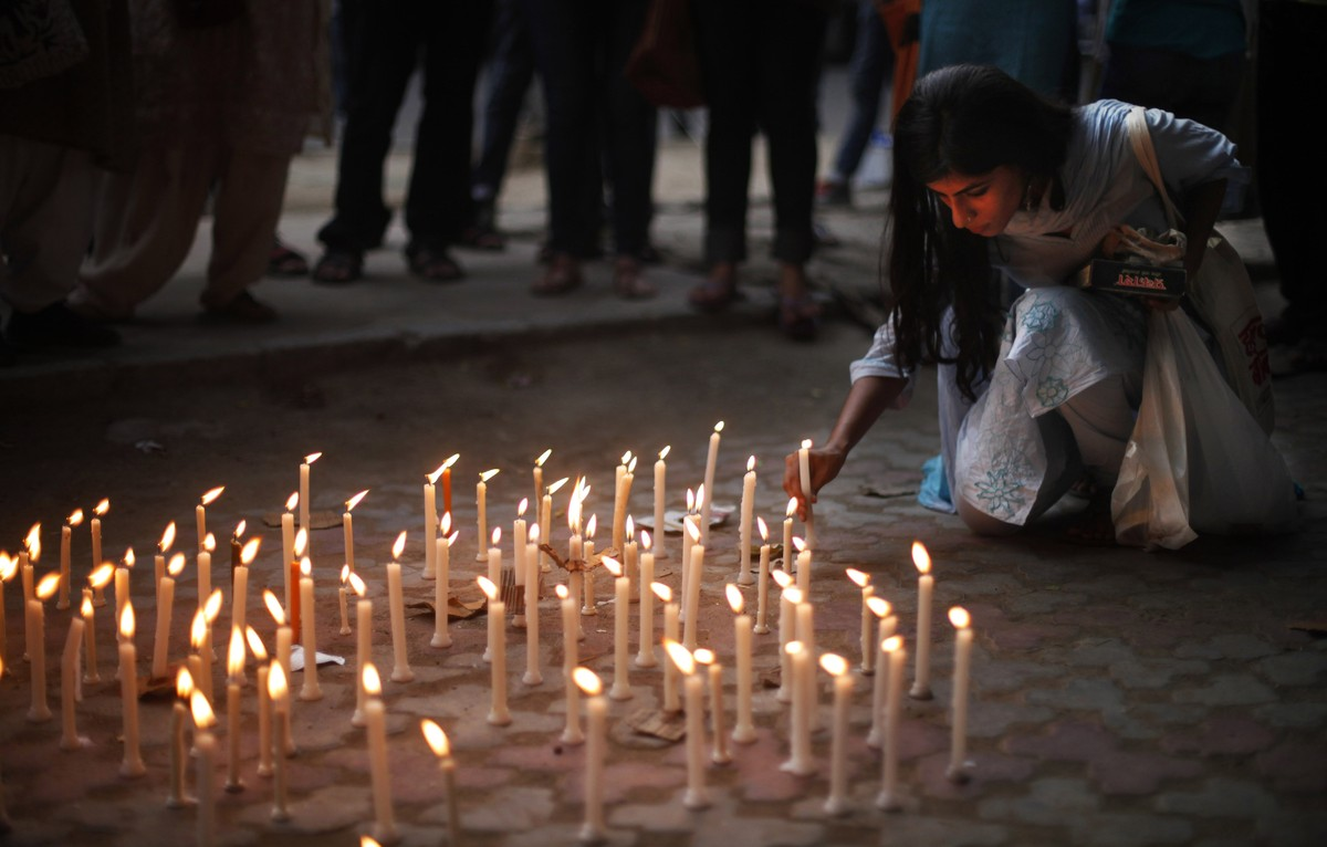 An activist places a candle on a pavement during a candle lit vigil to protest against the gang rape of two teenage girls, in
