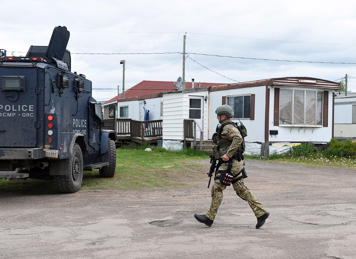 An emergency response team member runs past a trailer where murder suspect 24-year-old Justin Bourque resides in Moncton, N.B