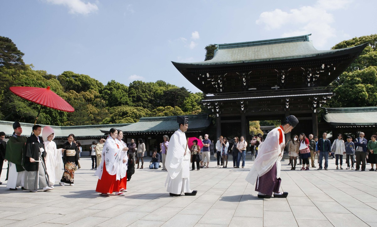 Shinto priests lead a Japanese couple under a parasol during a traditional wedding ceremony at Meiji Jingu Shrine in Tokyo. M