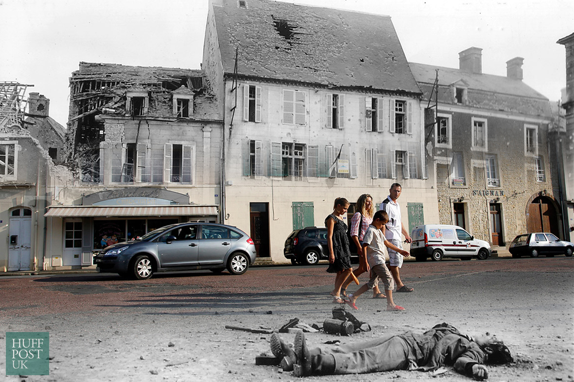Tourists walk by where the body of a dead German soldier once lay in the main square of Place Du Marche in Trevieres after th