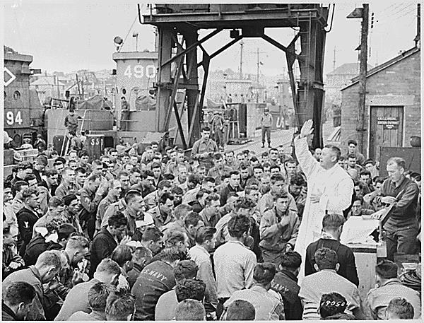 Father (Major) Edward J. Waters, Catholic Chaplain from Oswego, New York, conducts Divine Services on a pier for members of t