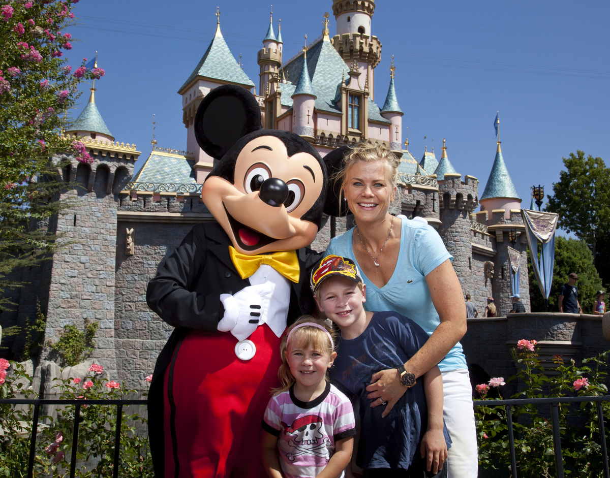 Actress Alison Sweeney and her children Benjamin, 7, and Megan, 3, pose with Mickey Mouse outside Sleeping Beauty Castle at D
