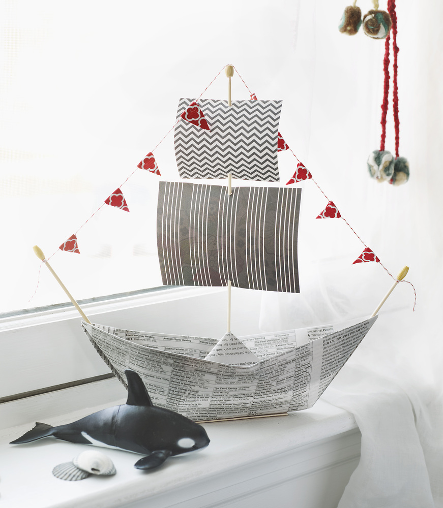 <br>Grab some bamboo skewers, string, a hot glue gun and dad's old newspapers and turn it into a boat he and the kids can pla