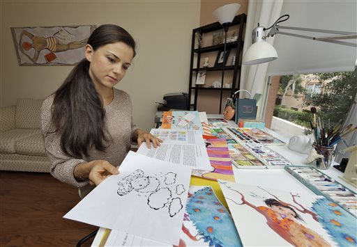 In this May 12, 2014 photo, Lina Safar displays some of her illustrations at her home in Tampa, Fla. Safar, originally from S