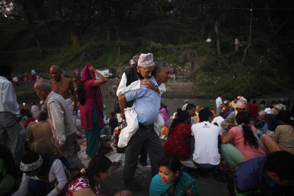 A Nepalese man carries his father to perform rituals during Kuse Aunsi, or Nepalese Father's day at the Gokarneshwar Hindu te