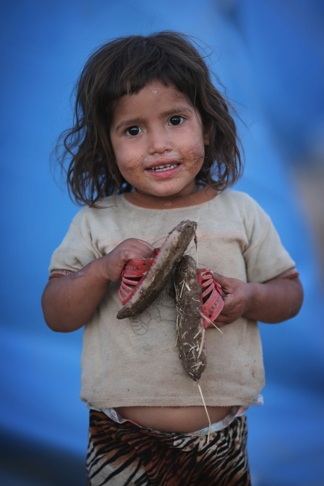 A young girl stands outside her tent at a temporary displacement camp set up next to a Kurdish checkpoint in Kalak, Iraq