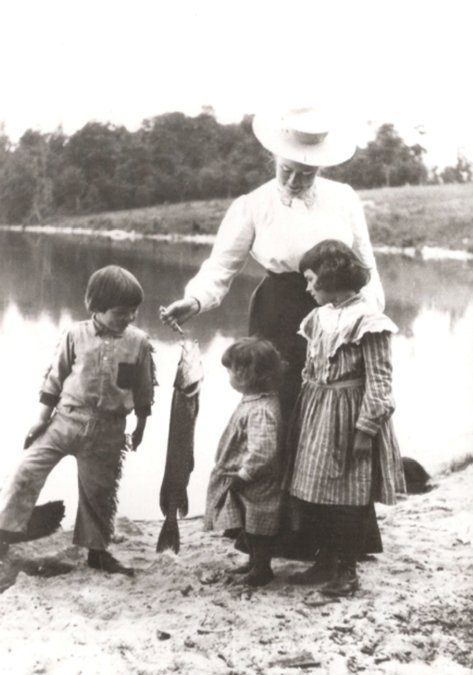 Grace Hall Hemingway showing Ernest and his sisters, Marcelline and Ursula, the seven-pound pike she has caught. Note that Er