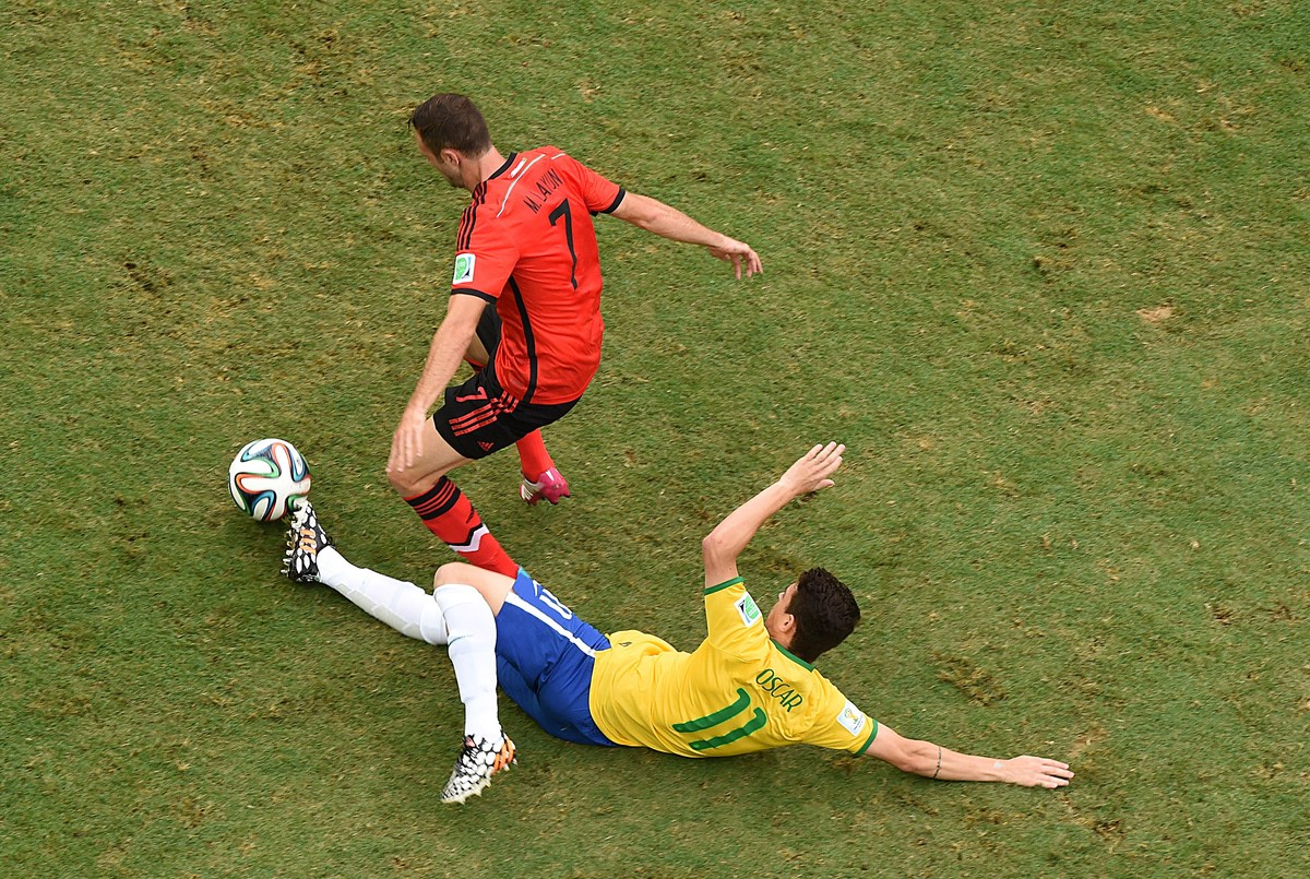 Brazil's midfielder Oscar (bottom) falls next to Mexico's defender Miguel Layun during a Group A football match between Brazi