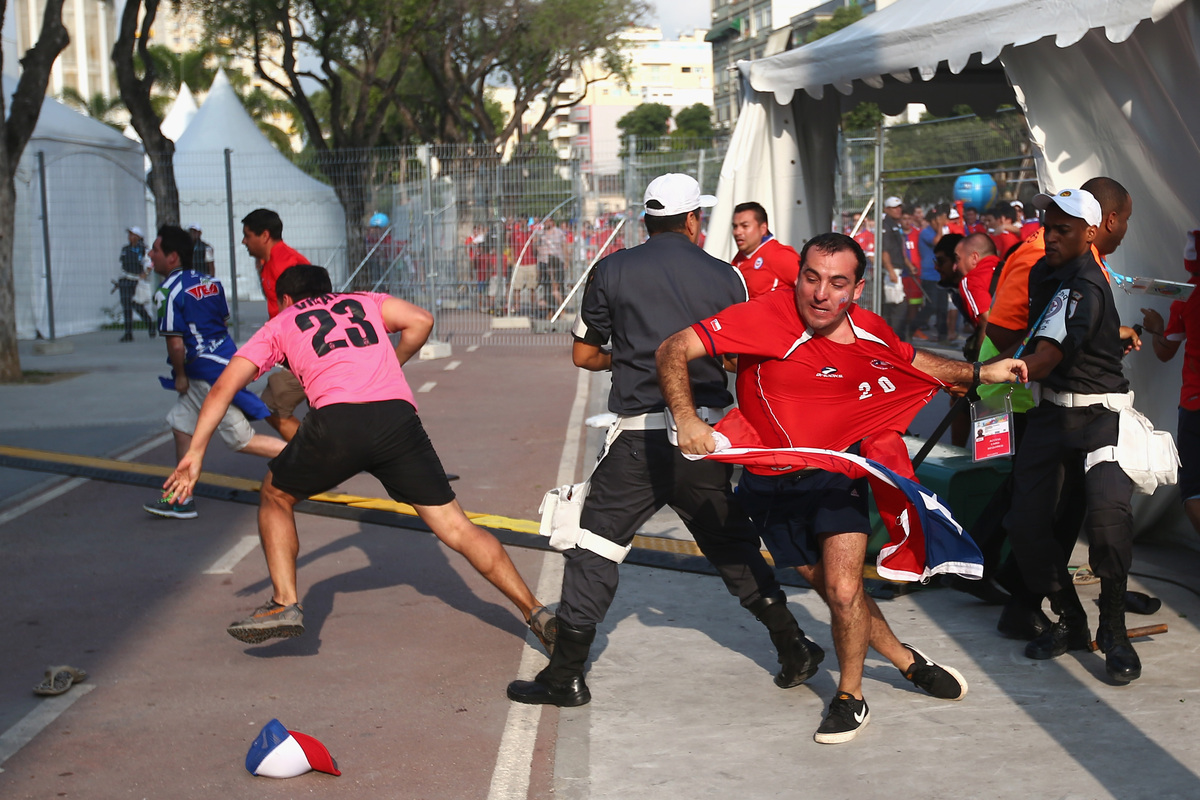 RIO DE JANEIRO, BRAZIL - JUNE 18:  Security personnel attempt to control Chilean fans outside the stadium prior to the kickof