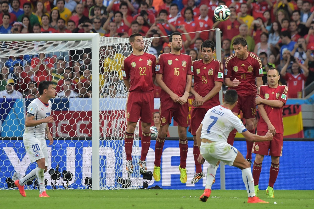 Chile's forward Alexis Sanchez (front) takes a free kick during a Group B football match between Spain and Chile in the Marac