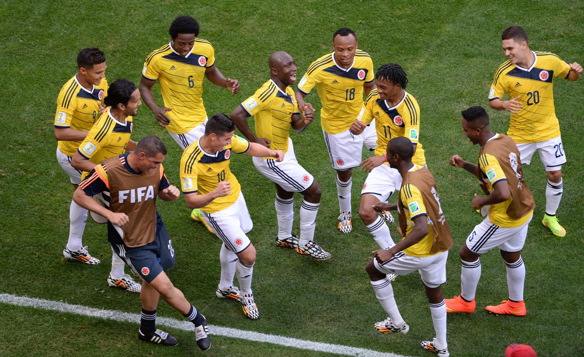 Colombia's players dance after scoring a goal during the Group C football match between Colombia and Ivory Coast at the Mane