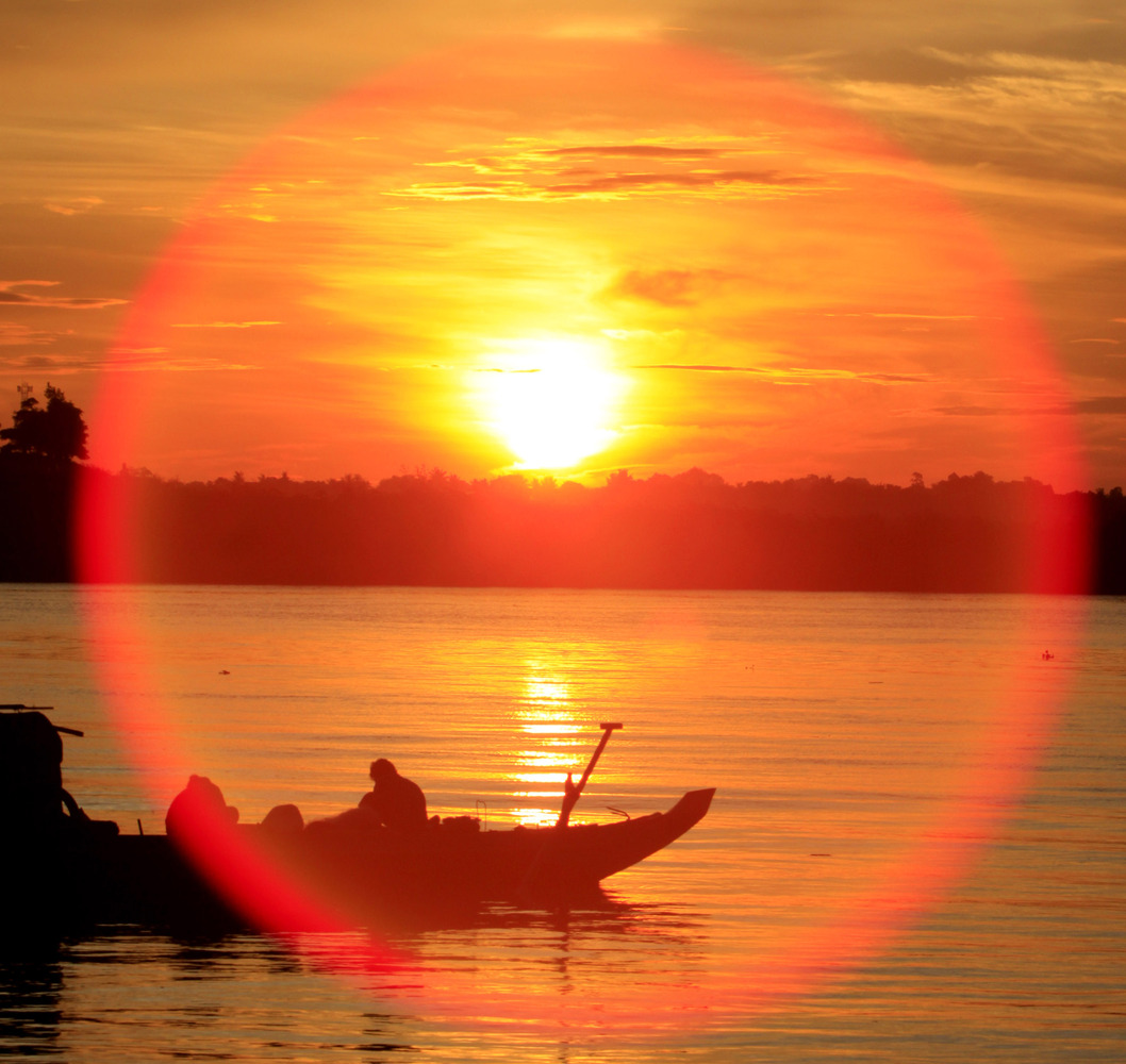 A reflection from the sunshine rises above a fishing wooden boat on the Tonle Sap river as Cambodian fishermen catching fish for their daily income in Phnom Penh, Cambodia, Wednesday, May 27, 2009. (Heng Sinith/AP)