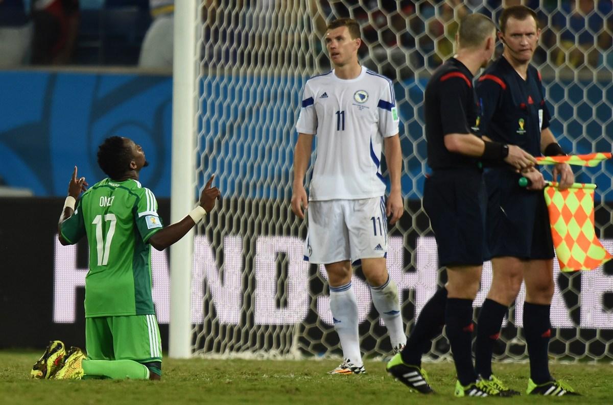 Nigeria's midfielder Ogenyi Onazi (L) celebrates winning as Bosnia-Hercegovina's forward Edin Dzeko react during the Group F